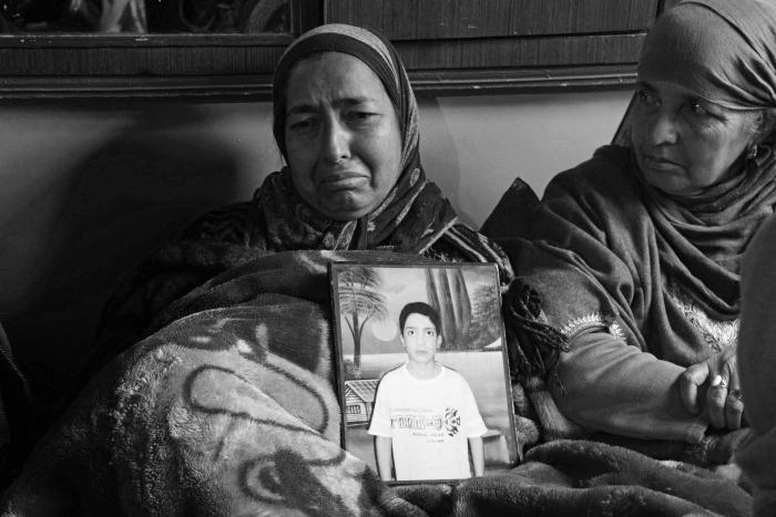 (Parveena displays a photograph of her teenage son Tehseen Nazir, who was killed by a police vehicle in Nowgam area of Srinagar city on January 7, 2020. Tehseen was on his way to tuition classes when a speeding police van crushed him to death). Kamran Yousuf/NewsClick