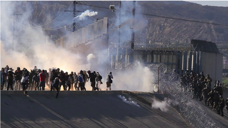 US border agents firing tear gas on migrants approaching the US border.