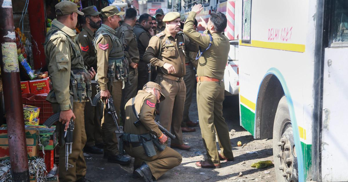 Police personnel inspect the site after a powerful explosion at a bus stand in Jammu on Thursday.