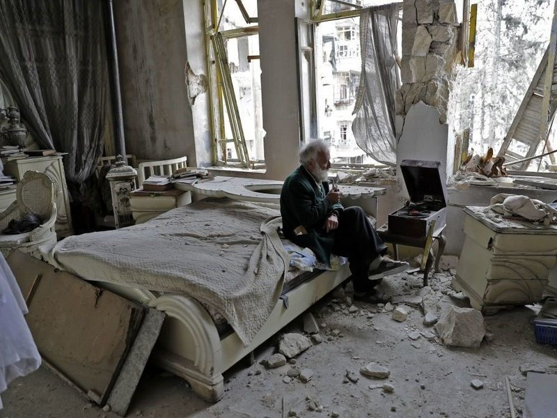 Abu Omar, 70, smokes his pipe as he sits in his destroyed bedroom listening to music on his gramophone in the neighbourhood of al-Shaar in Aleppo, Syria.