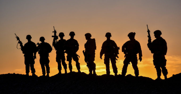 American soldiers in a remote post, silhouetted against the dimming Afghan sky.