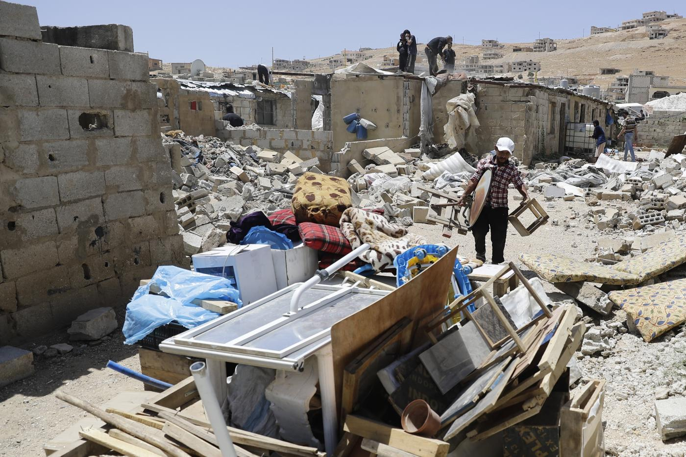 A Syrian man gathers his belongings as workers demolish cement block shelters at a refugee camp in the northeastern Lebanese town of Arsal, in the Bekaa valley