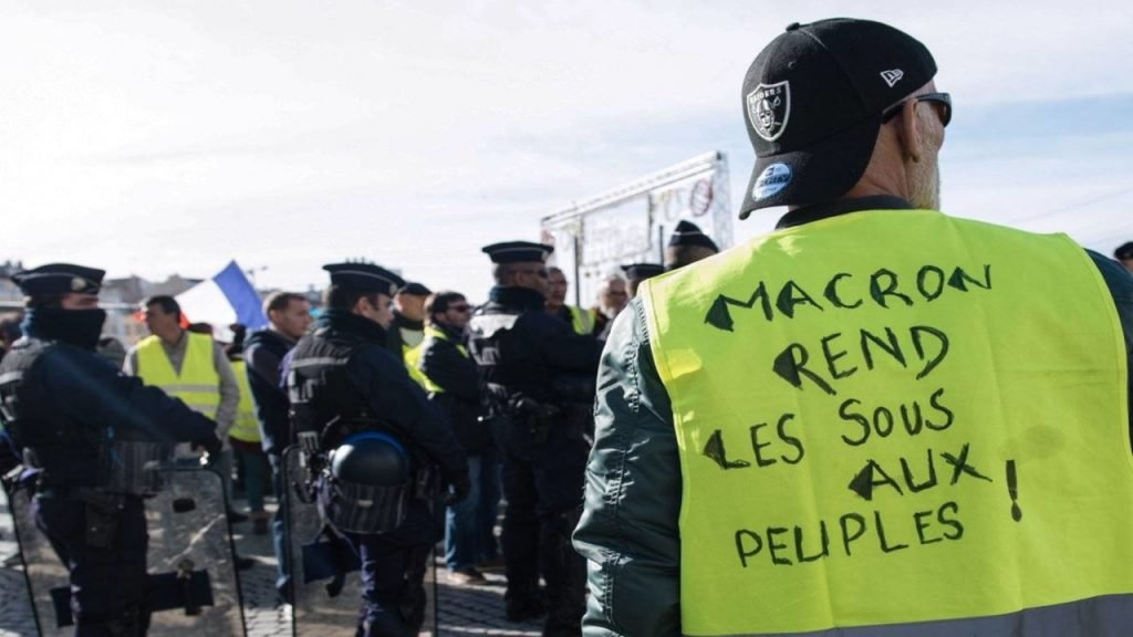 "A Yellow Vests protester. The slogan on his vest says. ""Macron, return the money to the people."""