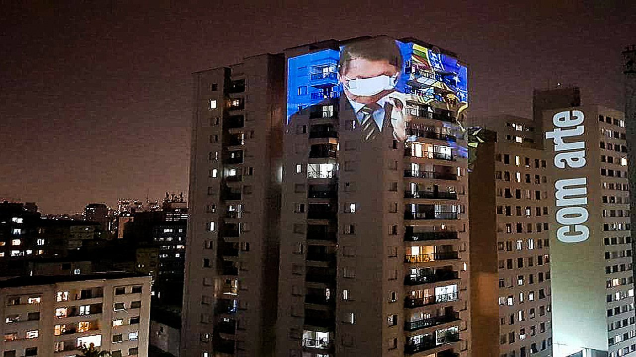 The government of Jair Bolsonaro has been severely criticized for its flawed handling of the COVID-19 pandemic. Here, an image of Bolsonaro failing to put on a mask properly is screened on a building as a mark of protest. Photo: Brasil De Fato