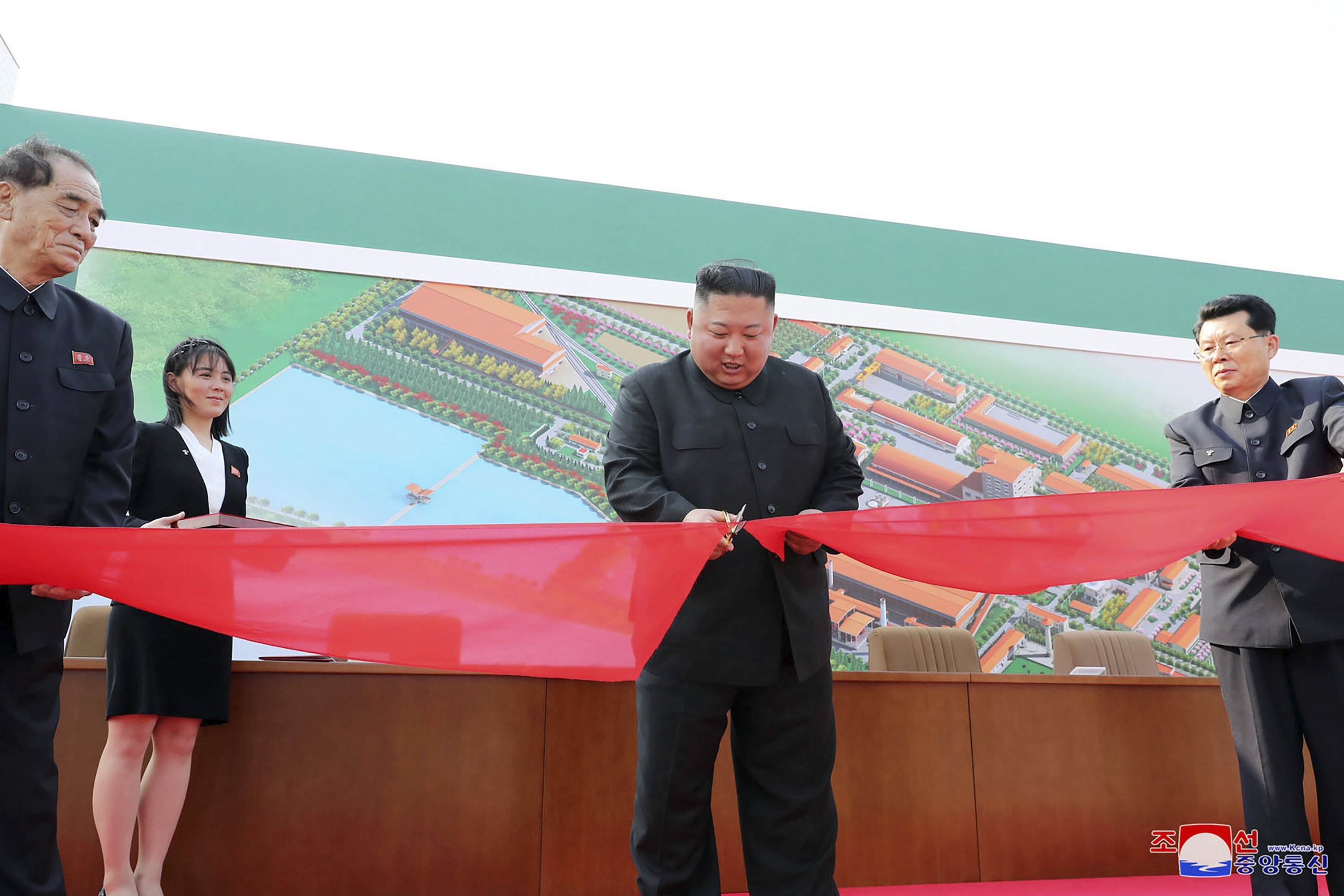 In this Friday, May 1, 2020, photo provided by the North Korean government, North Korean leader Kim Jong Un, center, cuts a tape, watched by his sister Kim Yo Jong, during his visit to a fertilizer factory in Sunchon, South Pyongan province, near Pyongyang, North Korea.