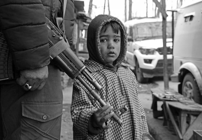 (Picture: A boy, after being removed from an encounter site, holds the gun of a policeman in Tral village of Pulwama where a gunfight between militants and government forces was underway on June 25, 2020.) Picture: Kamran Yousuf/NewsClick