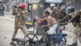 Policeman hits a civilian during a protest against the Citizenship (Amendment) Act
