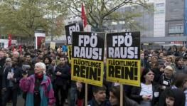 Supporters of a refugee home attend a gathering to protest against a demonstration of the Freedom Party of Austria (FPO) with a banner reading 'FPO out!'