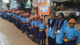 Students wearing BJP's symbols wait for Chief Minister Raghubar Das on Wednesday