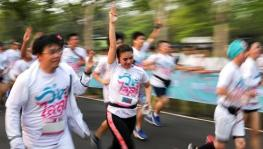Participants run while displaying the three finger salute as a mark of resistance and unity, at the 'Run against Dictatorship event in Bangkok on Sunday.