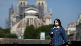 France bringing an end to lockdown on May 11 but it will not mean instant return to normal life. A woman, wearing a protective face mask, walks past Notre-Dame de Paris Cathedral, Paris, France, April 27, 2020.