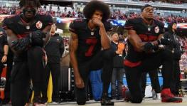 Colin Kaepernick of San Francisco 49ers and temmates kneel during the USA national anthem before an NFL match in 2016