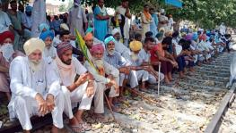 Farmers block railway track as they stage a protest against Farms bills, in Bathinda on Saturday.