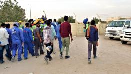Migrant workers heading to camp from drop point in Sonapur, UAE.