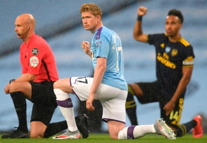 Manchester City and Arsenal FC players take the knee during their Premier League match