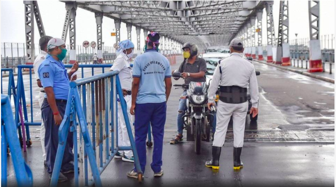 Police personnel stop commuters at Howrah Bridge, during the complete biweekly lockdown in the wake of coronavirus pandemic, in Kolkata.   | Photo Credit: PTI