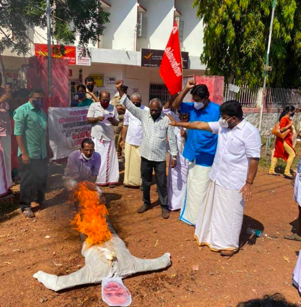 Farmers led by KK Ragesh, Rajya Sabha Member and joint secretary of All India Kisan Sabha, burn effigy of Modi in front of head post office at Kannur