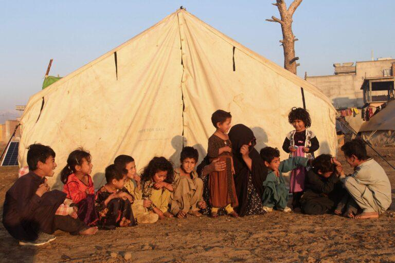 Internally displaced children sit outside a tent at a refugee camp, Khost province, Eastern Afghanistan, November 17, 2020