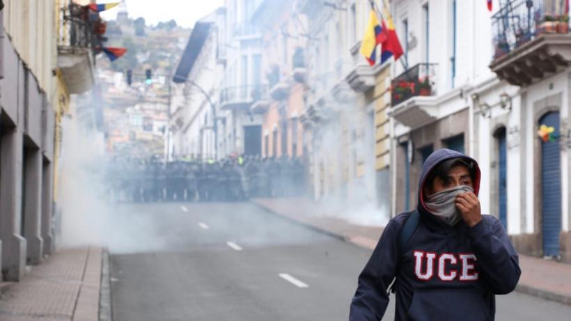 Student runs from police in Quito, Ecuador during mass mobilizations against the neoliberal economic reforms of the Moreno government.
